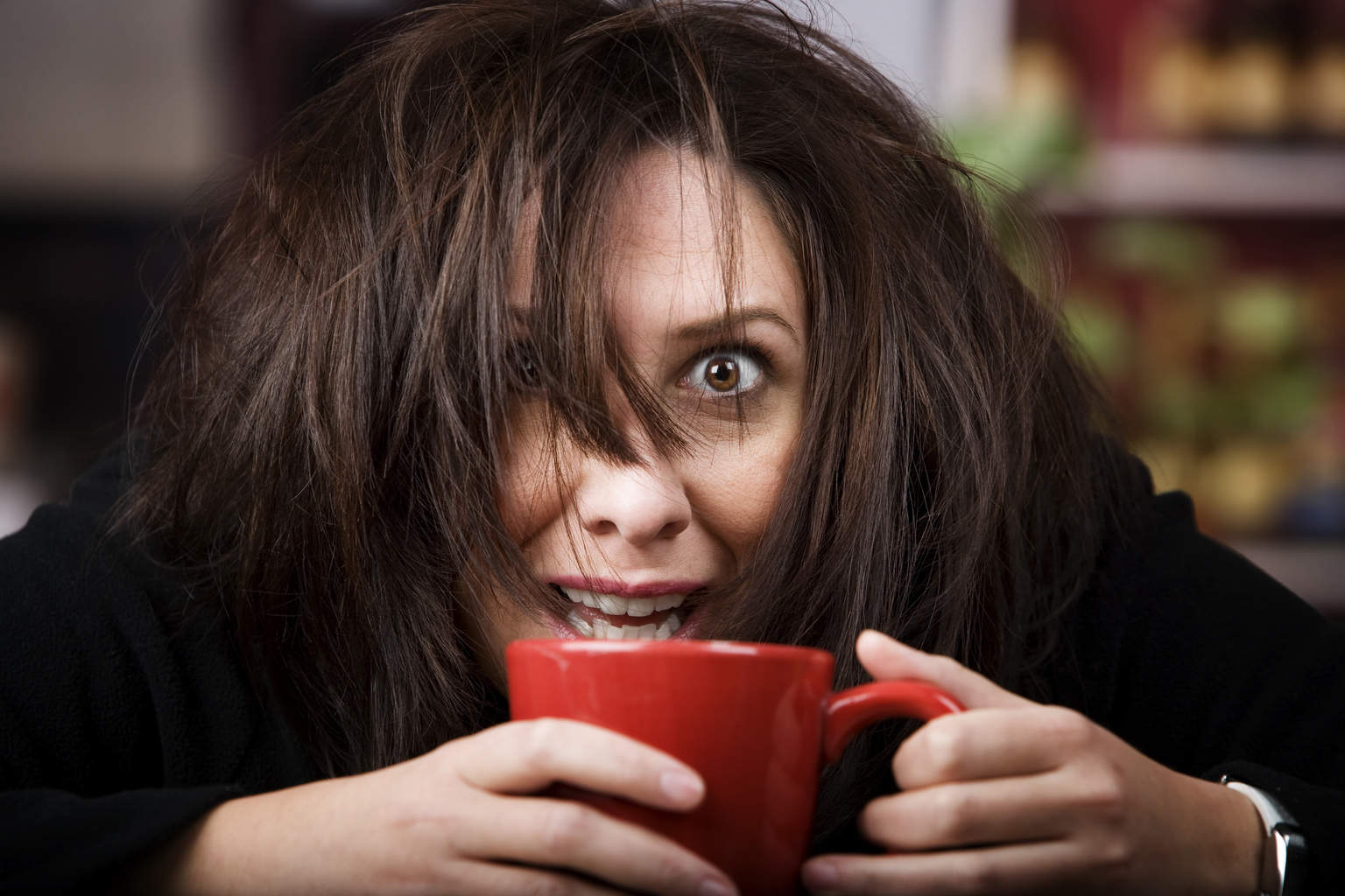 Half awake woman cradling a mug of coffee