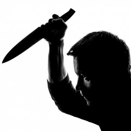 Man holding knife in threatening way about to stab