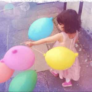 three year old in party dress holding balloons